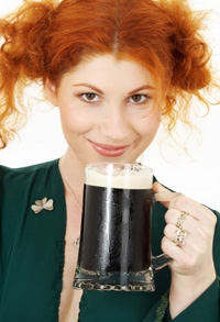 A young Irishwoman holds up a pint of stout to the camera