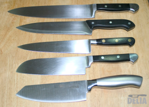 Five chef knives of various designs displayed on a wooden table