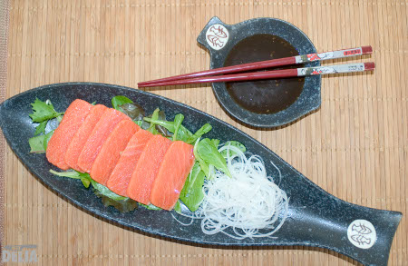 Salmon sashimi served with ponzu dipping sauce, baby herb leaves and shredded daikon