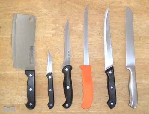 A variety of kitchen knives displayed on a wooden table