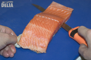 Filleting knife slicing between the skin and flesh of a fillet of salmon