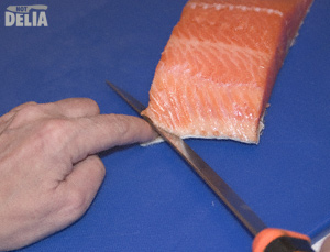 Filleting knife inserted between the skin and flesh of a fillet of salmon