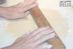 Pastry being rolled flat on a floured white food preparation board with a wooden rolling pin