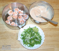 Steel dishes containing cooked prawns and Marie Rose sauce, and chopped lettuce, onions, cucumber and lime wedges on a small plate