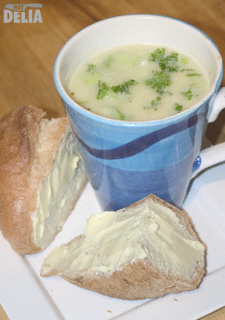 A mug of thick leek and potato soup with thickly-buttered crusty bread