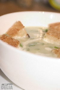 Close-up of a bowl of leek and potato soup with croutons and extra herbs