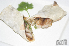 A filled Chinese pancake cut diagonally and presented on a white square plate