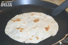 A Chinese pancake frying in a pan