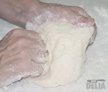 Pancake dough being kneaded on a floured white chopping board