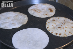 Four Chinese pancakes frying together in a pan