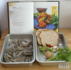 Prawns, bread, garlic, chillis, ginger, coriander and egg in two aluminium trays, with an open cookbook behind