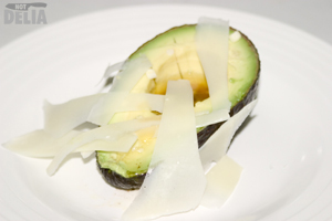 Half an avocado, drizzled with vinaigrette and topped with Parmesan cheese shavings