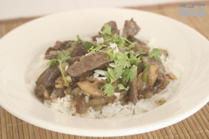 Ostrich fillet strips in black pepper sauce, on a bed of rice in a dish
