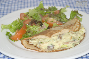 Savoury buckwheat pancake with bacon, mushroom and leek in parsley and mustard sauce and a side salad