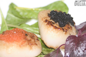 Seared scallops with butter and garlic on a bed of leaves