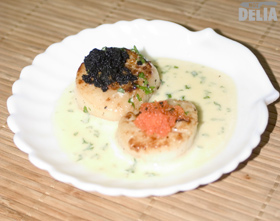 Seared scallops with two kinds of caviare in a cream and brandy sauce on a scallop-shell plate