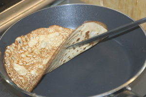 A cooked pancake, lifted from the pan on one side to show the cooked underside