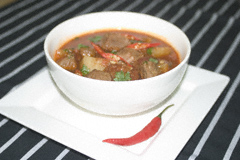 Goulash soup with a sprinkling of coriander and red chilli slices in a white bowl on a white plate