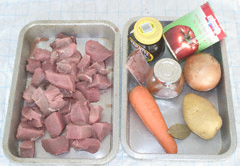 Stewing steak, carrot, potato, onion, tinned tomatoes and other ingredients in two aluminium roasting tins