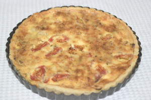 A quiche in its baking tin, just after emerging from the oven