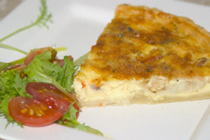 A slice of bacon quiche with a salad garnish