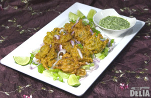 Bhajis on a plate with a small dish of coriander and coconut dip