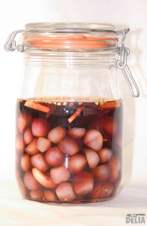 A pickling jar with onions, garlic and chillies in red wine vinegar