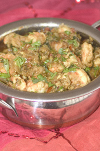 Prawn pathia in a steel presentation karahi on a sequined cloth