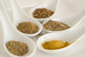 Cumin, coriander, red chilli, garam masala and turmeric powders presented in Chinese soup spoons on a plate