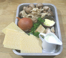 Mushrooms, onions, sheets of lasagne, a small jug of milk, butter, Parmesan cheese and parsley in an aluminium roasting tin