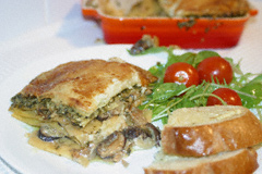 Mushroom and pesto lasagne on a plate with rocket and tomato salad and some garlic bread