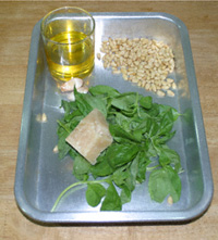 Basil, olive oil in a glass, pine nuts and Parmesan cheese, all in an aluminium roasting tin
