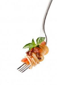 A forkful of spaghetti bolognese on a fork, garnished with a tiny sprig of basil