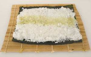 A sheet of nori on a makisu, spread with a layer of sushi rice and with a thin strip of wasabi