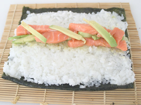 Nori sheet with sushi rice, plus a filling of raw salmon and avocado