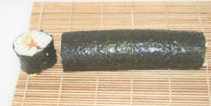 Nori roll lying on the makisu with one end trimmed off