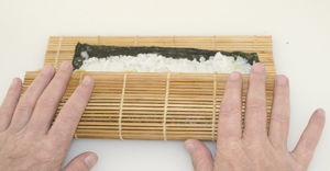 A nori roll nearing the end of the rolling process