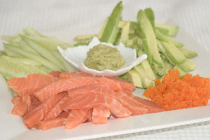 Batons of salmon, avocado, and cucumber with salmon roe and wasabi presented on a square plate