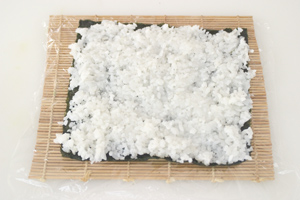 A nori sheet placed on a cling film-covered makisu (rolling mat) and covered with a layer of sushi rice