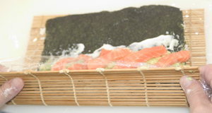 A California roll (uramakizushi) in the early stages of being rolled