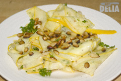 Thinly-sliced strips of yellow courgette or zucchini with toasted pinenuts, lime juice and coriander on a white plate