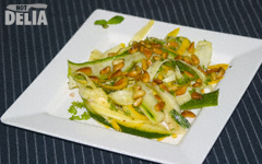 Thinly-sliced strips of green and yellow courgette or zucchini with toasted pine nuts, lime juice and coriander on a white plate