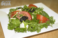 A salad made with courgette, rocket leaves, cream cheese, tomatoes, black olives, parsley and dressing