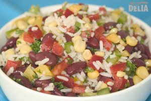 A bowl of rice salad made with peppers, sweetcorn, kidney beans and parsley