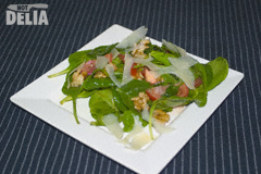 Rocket salad with tomatoes, Parmesan cheese shavings and walnuts on a white plate