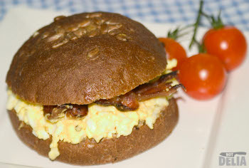 A brown wholemeal roll topped with sunflower seeds and filled with egg mayonnaise and streaky bacon