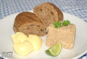 Mushroom paté, served on a plate with wholemeal bread, butter and a lime wedge