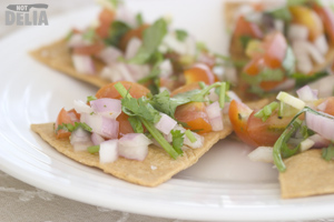 Tostada triangles topped with a tomato, onion and coriander salsa