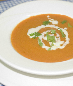 A bowl of carrot and orange soup, garnished with a swirl of cream and sprinkled with fresh coriander