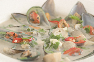 A bowl of mussel soup with straw mushrooms, red chillis and coconut milk